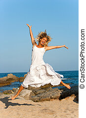 Attractive woman in white jumping outdoors.