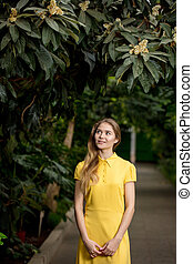 attractive woman in yellow dress in the garden