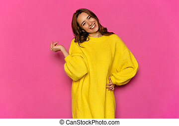 Attractive woman in yellow dress on pink background.