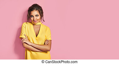 Attractive woman in yellow dress posing on pink background in studio. Looking at camera