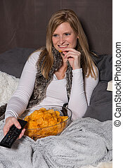 Attractive woman is eating chips and has remote control in hand