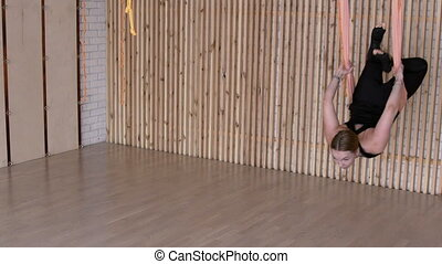 Attractive woman is practicing anti gravity yoga in hammock...