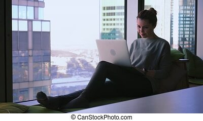 Attractive woman is sitting by the window with business center view, opening her laptop and starting type on a keyboard
