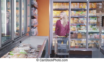 Attractive woman is walking in supermarket and confident...
