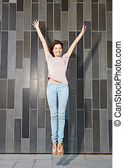 attractive woman jumping in air with arms extended