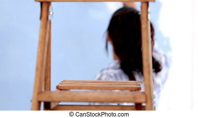 Attractive woman jumping to paint h