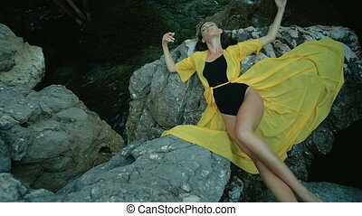 Attractive woman lies on rock by sea shore in summer day.