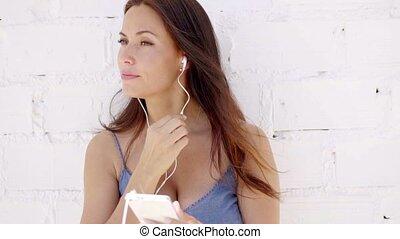 Attractive woman listening to music on earphones