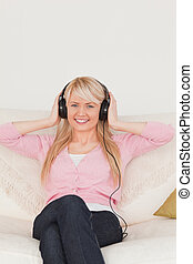 Attractive woman listening to music on her headphones while sitting on a sofa in the living room