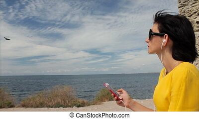 Attractive woman listening to music with headphones on smartphone on a background of sea and the ruins of the ancient city