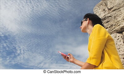 Attractive woman listening to music with headphones on smartphone on a background of sky and the ruins of the ancient city