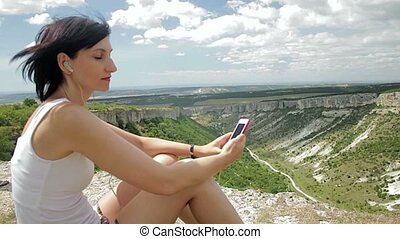 Attractive woman listening to music with headphones on smartphone on a background of mountains