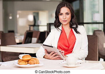 Attractive woman looking at camera while sitting at ...