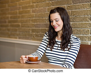 Attractive Woman Looking At Coffee Cup In Cafe