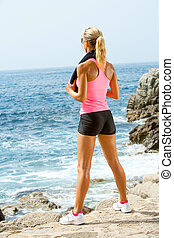 Attractive woman looking at sea after exercise.