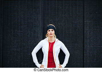 Portrait of attractive young woman looking confident in sportswear. Female runner outdoors.