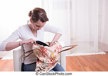 attractive woman looking into bag