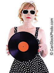 Attractive woman looks like a pinup, holding a vinyl record in her hands.