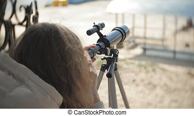 Attractive woman looks through a telescope in a forest on...