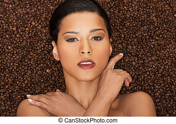 Attractive woman lying in coffee grains. Fron view. Closeup.