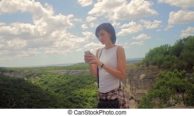 Attractive woman make selfie on smartphone on a background of mountains