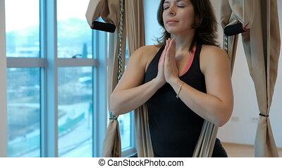 Attractive woman meditates padmasana pose hammock in studio indoors.