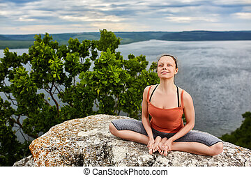 Attractive woman meditating in lotus posture sitting on the rock above river.