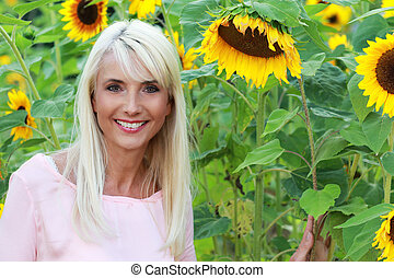 Attractive woman middle age in sunflower field