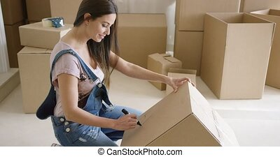 Attractive woman moving house and packing her personal...