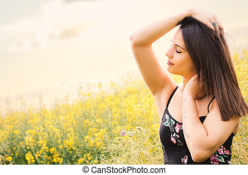 Attractive woman next to yellow flower field.