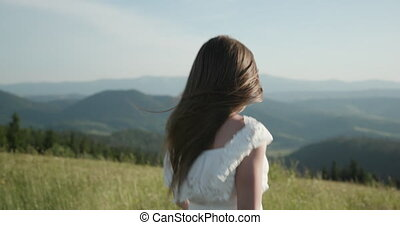 Attractive woman on a mountain peak with her long hair blowing in the wind smiling and trying to keep her hair off her face