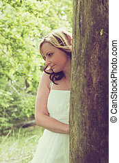 Attractive woman on a tree trunk