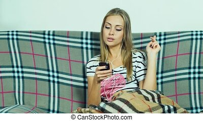 Attractive woman on the couch listening to music with headphones