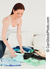 Attractive woman packing her suitcase