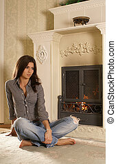 Attractive woman  near the fireplace