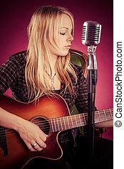 Attractive woman playing acoustic guitar