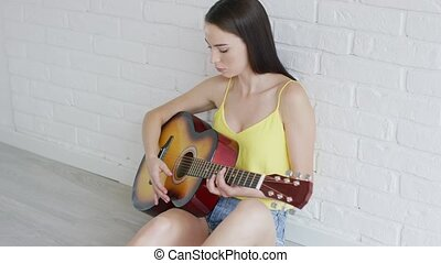 Attractive woman playing guitar near wall - Beautiful young...