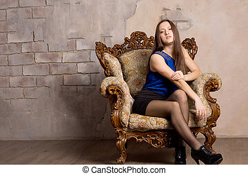 Attractive woman posing in an antique armchair