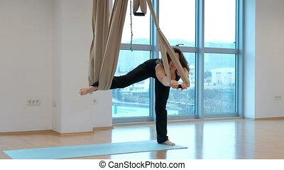 Attractive woman practices gravity yoga in studio indoors.