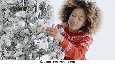 Attractive woman preparing the tree for Christmas