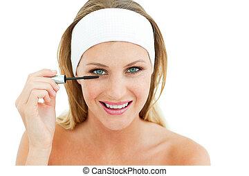 Attractive woman putting mascara