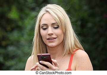Attractive woman reading an sms on her mobile
