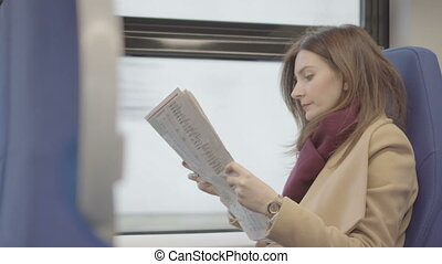 attractive woman reading magazine during train travel,...