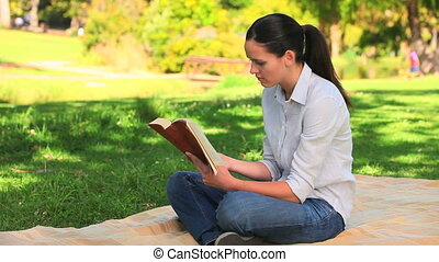 Attractive woman reading outdoors
