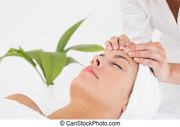Attractive woman receiving facial massage at spa center
