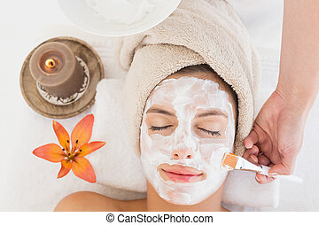 Attractive woman receiving treatment at spa center -...