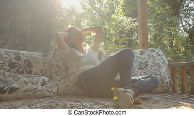 Attractive woman relaxing and sitting on pillows in the gazebo located in the forest