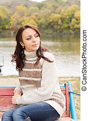 Attractive woman relaxing at the side of a lake