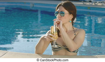 Attractive woman relaxing in pool, drinking cocktail on vacation