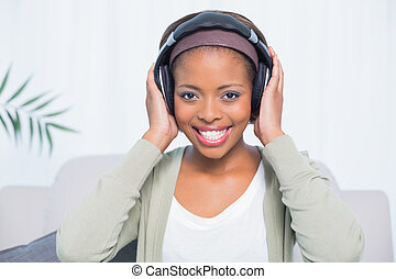 Attractive woman relaxing with headphones while sitting on a sofa in the living room